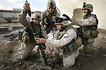 A mortar team with 2nd Platoon Golf Company 2nd Battalion 5th Marines drops 60mm mortars as the platoon repulses an attack on the Al-Anbar provincial Government Center by teams of insurgents carrying small arms and improvised shoulder-fired rockets, killing at least three of the attackers on January 15, 2005 in Ramadi, Iraq. The Government Center which houses the office of the provincial governor and administration has been a frequent target of the insurgents especially as the January 30th election approaches.