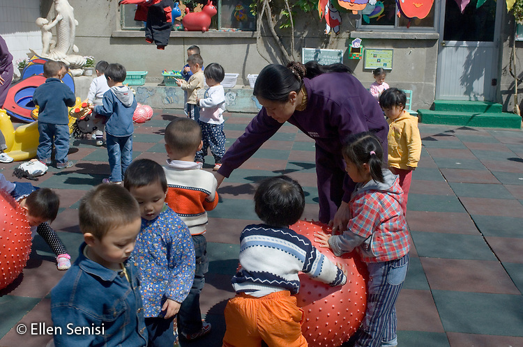 Beijing, China (Hutong area in Northwest Beijing; Gulouxi Street) / April 20, 2005.Guozishi Kindergarten (for students aged 2 through 6). School provides day care and week care (week care provided to working parents who opt to bring their children home only on weekends). .Teacher breaks up dispute over toy during free time in the courtyard..© Ellen B. Senisi