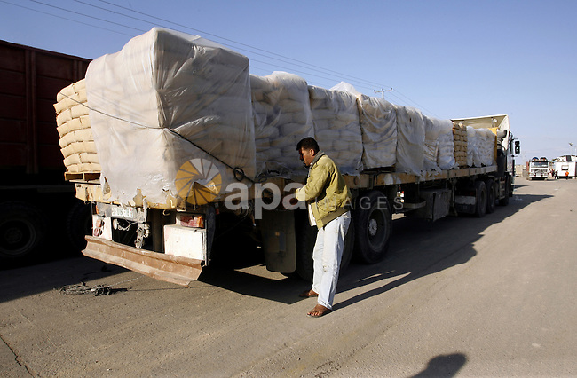 A Palestinian worker removes the straps around bags of cement loaded on a truck that entered the Gaza Strip from Israel through the Kerem Shalom crossing in Rafah in the southern Gaza Strip on November 5, 2014. UN peace envoy Robert Serry announced on November 4 that the temporary reconstruction mechanism for the war-torn Palestinian territory had begun operations, under the auspices of the newly formed Palestinian unity government, noting the urgency in providing cement and other materials to tens of thousands of damaged homes in Gaza ahead of winter. Photo by Abed Rahim Khatib