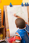 Education preschool 3-4 years old art activity boy in smock drawing human figures at easel using marker