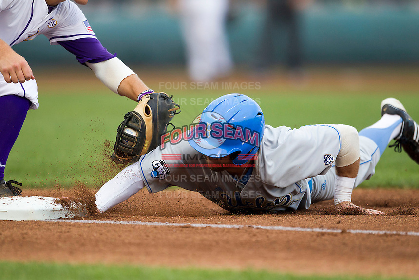 UCLA Bruin outfielder Eric Filia (4) dives back to first base in the first inning of Game 4 of the 2013 Men's College World Series against the LSU Tigers on June 16, 2013 at TD Ameritrade Park in Omaha, Nebraska. UCLA defeated LSU 2-1. (Andrew Woolley/Four Seam Images)