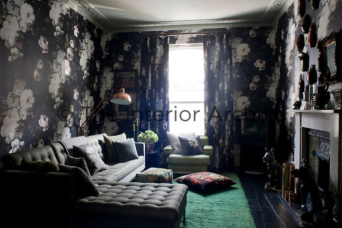 A Knoll sofa in the living room is surrounded by dark, floral wallpaper designed by Ellie Cashman. The design was also printed on velvet for the curtains