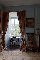 A delicately turned table and chair sit in an alcove of Bishop Leslie's Room overlooking the grounds