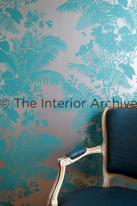 A silk covered period chair against blue floral pattern chinoiserie wallpaper