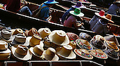 Boats cruising throught the jamb-packed Damnoen Saduak Floating Market in Ratchaburi (near Bangkok). The boat in the foreground displays some of the many styles and colors of hats one may purchase to keep the sun at bay, while the Thai women in their own brightly colored hats can be seen floating past in the background as they eat their lunch with chopsticks. Selected for Photographic Center - Capital District - 2009 Members' show.
