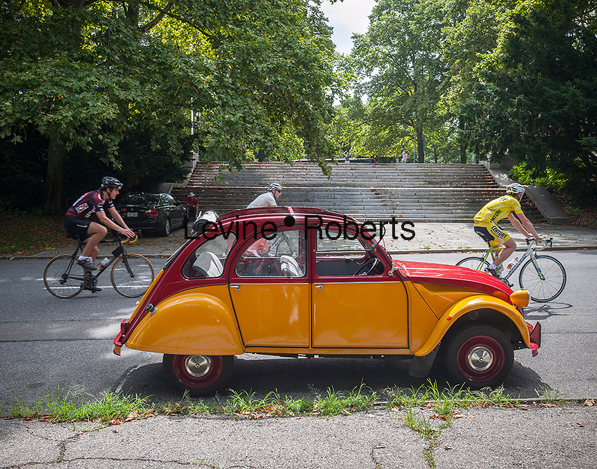 Bicyclists pass a 2CV prior to the Greater New York Citorën and Velosolex Touring Club  Bastille Day Rendez-Vous, seen on Riverside Drive in New York on Sunday, July 14, 2013. The parade of over a dozen Citroëns, including 2CV, DB series models, a truck and a traction avant started on Riverside Drive and traveled through the streets of Manhattan. The owners are dedicated to restoring and caring for their vehicles and share tips and information on repairing and restoring them. (© Richard B. Levine)