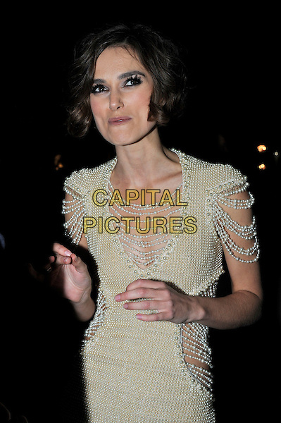 KEIRA KNIGHTLEY.'Never Let Me Go' Opening Gala of the London Film Festival the Odeon, Leicester Square, London, England..October 13th 2010.half length pearl beads pearls dress cream cut out away sides sleeves Chanel yellow look closer circle of shame moustache mustache facial hair smokey eyes make-up funny.CAP/IA.©Ian Allis/Capital Pictures.