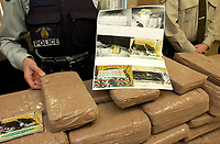December 04,  2002, Montreal, Quebec, Canada; <br /> <br /> A  Montreal City (SPCUM) Policeman show drug, guns and money<br /> seized during a recent drug bust,to the medias,<br />  December 04, 2002 in Montreal, Canada.<br /> <br /> 15 people presumably involveld in a 2 billion Can $ drug deal, where arrested after a joint operation by the RCMP, Quebec Province and Montreal City Police.<br /> <br /> <br /> <br /> (Mandatory Credit: Photo by Sevy - Images Distribution (©) Copyright 2002 by Sevy<br /> <br /> NOTE :  D-1 H original JPEG, saved as Adobe 1998 RGB.<br />  Uncompressed and uncropped original  size file available on request.