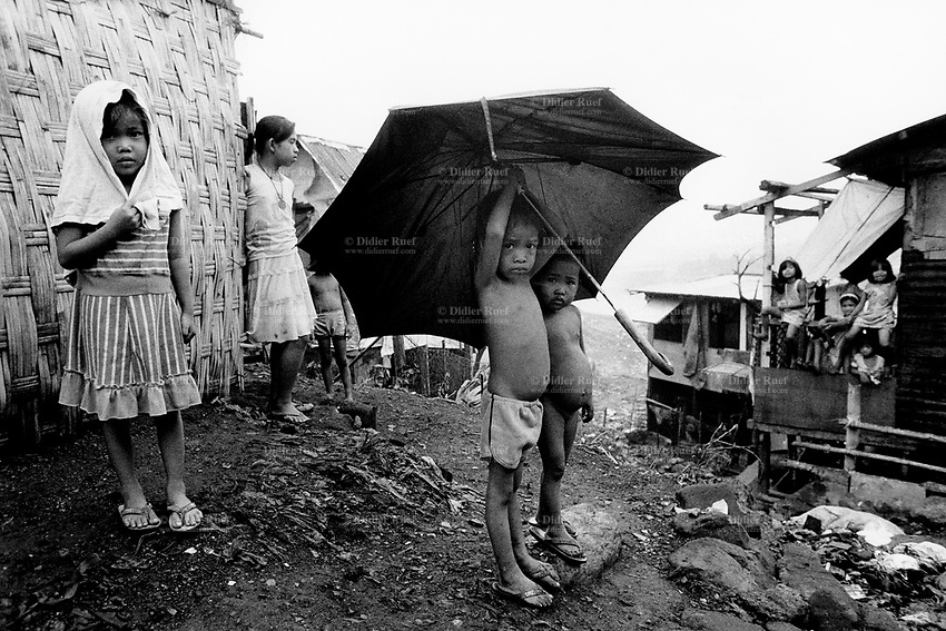 Philippines. Luzon Region. Manila. Tondo area. Smokey mountain is a rubbish dump. Life on a garbage heap. Group of children on a rainy day. A small malnourished boy is fully naked, another wears a pair of shorts and is stripped to the waist.  © 1992 Didier Ruef .