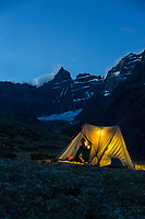 Camper looks out of tent at the night sky. Mount Igikpak is the highest peak in the Schwatka Mountains region of the Brooks Range, Gates of the Arctic National Park, Alaska