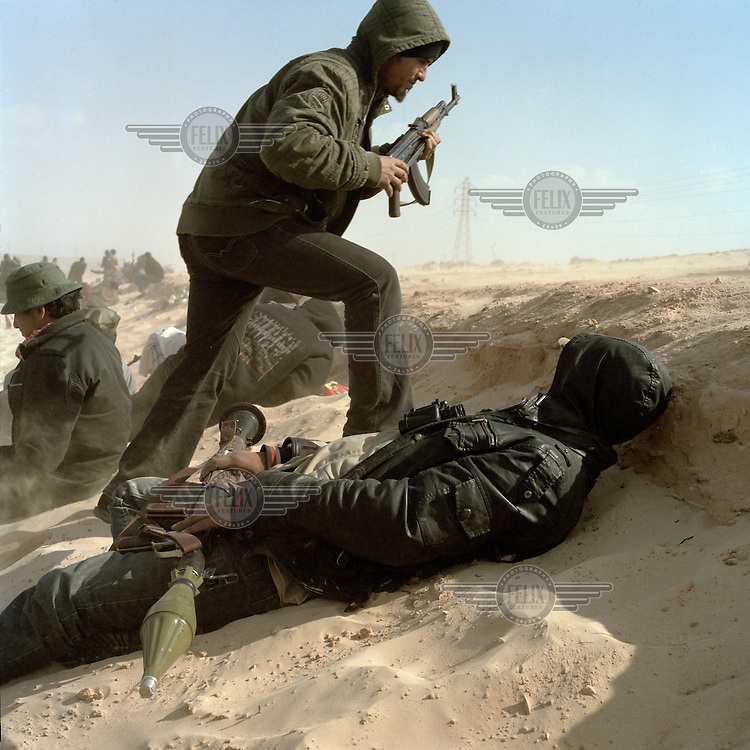 Rebel fighters react to incoming shells fired by Gaddafi froces positioned 3km away on the outskirts of Ajdabiya. One fighter lies down holding an RPG. On 17 February 2011 Libya saw the beginnings of a revolution against the 41 year regime of Col Muammar Gaddafi.