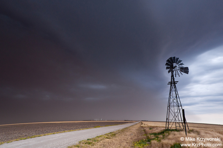 A thunderstorm produces a dust storm behind a windmill along a dirt road in the Amy, KS, June 2, 2012
