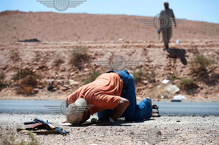 A rebel fighter takes a break for afternoon prayer on the northern outskirts of Bani Walid.