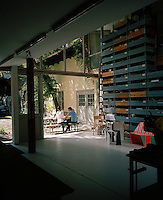 Designers Stefan and Saskia Diez sitting at a table in the garden outside their open plan studio