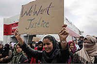 "Pictured: An Afghan woman with a placard that reads ""We Want Justice"" in Piraeus port Tuesday 08 March 2016<br />