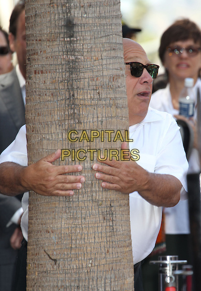 Danny DeVito.Danny DeVito Honored On The Hollywood Walk Of Fame Held On Hollywood Blvd., Hollywood, California, USA..August 18th, 2011.half length white shirt sunglasses shades hands hiding behind tree trunk funny mouth open scared .CAP/ADM/RE.©Russ Elliot/AdMedia/Capital Pictures.