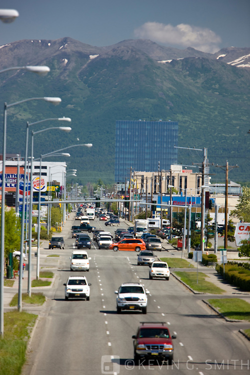 Busy midday traffic in Midtown Anchorage, looking east along Northern Lights blvd. towards the Chugach Mountains, Anchorage, Southcentral Alaska, USA.