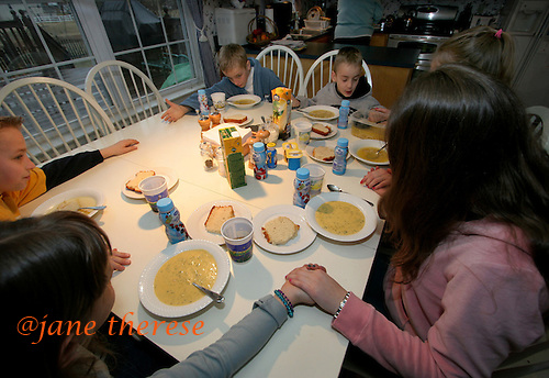 The Salem children of Telford, Pa., L-R; Sophia 8 (bottom left), Jake (dark sleeves, left) 12, reaches across the table for his twin brother Sam's hand. Sitting next to Sam (top left) is Joseph twin to Sophia, Selene 13 (hidden top right) and her twin sister Julianne (bottom right), say prayers before lunch on a cold Thursday March 2, 2006 afternoon. The Salem children, 3 sets of twins, are from Russia. Sophia and twin Joseph were adopted at 11 months of age by Hythem and his wife Lisa. The other twins, Selene and Julianne 13 along with Sam and Jake, were adopted just 20 months ago. All children are thriving in school, socially and physically. photo by jane therese