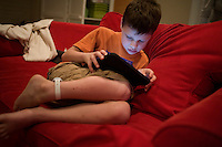 "Jack Ursitti looks at photos and listens to music on an iPad during a ""sensory break"" in his home in Dover, Mass., on Monday, July 25, 2011.  Jack has been diagnosed with autism.  After school at his home, Jack works with his teacher and a therapist to do educational and independent leisure activities. Periodically Jack takes ""sensory breaks"" to stop activity and play independently, allowing him to return to his tasks with greater concentration. During the ""sensory breaks"" Jack does a variety of things, including looking at his reflection, making faces, jumping on a small trampoline or cushions, or play with an iPad...Jack Ursitti wears a small GPS ankle bracelet at all times in case he runs off from his family or caretakers. The device will be activated if he goes missing, allowing police and other searchers to find him."
