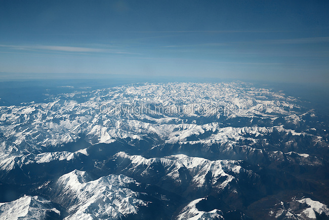 Aerial view of the Pyrenees mountains, dusted with snow, seen from an aeroplane, South West France. The Pyrenean chain separates France from Spain. Picture by Manuel Cohen