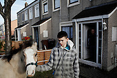 "Dublin, Ireland, January 5, 2011:.Luke, 12,  with his horse by their home on Bell Camp housing estate..Since the beginning of crisis, between 10 and 20 thousand horses have become homeless or went in the hands of the youths in urban areas. Lots of Irish people who used to buy horses for fun during the boom years of ""Celtic Tiger"", now are abandoning them faced with expenditure of 35 Euro a week to properly maintain a horse. This animal previously worth 2000 Euro now can be purchased for as little as 80 Euro. New owners keep their horses in city greens, city ruins, or their house gardens, in very bad conditions. Most do not get much food, many are starving, dying, being mistreated..(Photo by Piotr Malecki / Napo Images)..Dublin, Irlandia, 5/01/2011:.Luke, 12 lat i jego kon przed domem na osiedlu mieszkaniowym Bell Camp..Od poczatku kryzysu od 10 do 20 tysiecy koni zostalo wyrzuconych na ulice przez wlascicieli nie chcacych placic okolo 35 Euro/tydzien za ich utrzymanie. Wpadaja one czesto w rece mlodziezy z ubogich dzielnic miasta, ktora handluje nimi, bije, glodzi, trzyma w skrajnie trudnych warunkach, w przydomowych ogrodkach lub ruinach budynkow i szaleje na nich po miescie. Kon, ktory byl wart 2000 Euro teraz moze byc kupiony za 80. .Fot: Piotr Malecki / Napo Images."