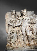 Roman Sebasteion relief sculpture of emperor Claudius and Agrippina, Aphrodisias Museum, Aphrodisias, Turkey.  Against a grey background.<br /> <br /> Claudius in heroic nudity and military cloak shakes hands with his wife Agrippina and is crowned by the Roman people or the Senate wearing a toga. The subject is imperial concord with the traditional Roman state. Agrippina holds ears of wheat: like Demeter goddess of fertility. The emperor is crowned with an oak wreath, the Corona civica or &ldquo;citizen crow&rdquo;, awarded to Roman leaders for saving citizens lives: the emperor id therefore represented as saviour of the people.