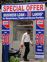 Businessman is walking under the Business loan special offer advert for Manufacturers, traders and service providers in Madras, India