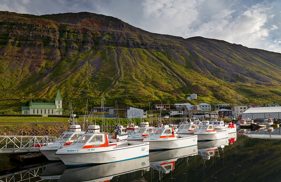 Fishing boats at dock in Sudureyri below Ufsir mountain, West Iceland, Iceland