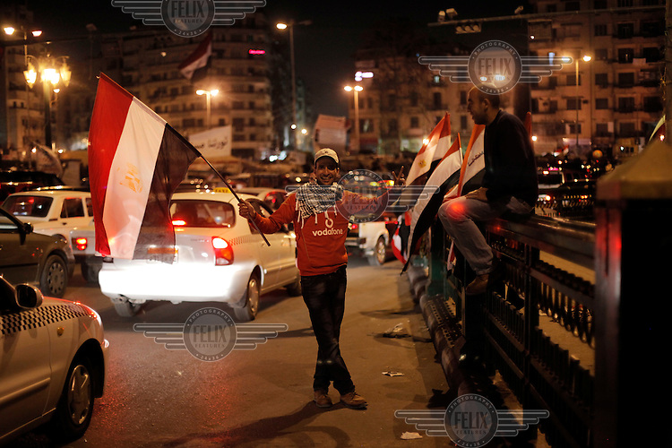 Men seling flags in Tahrir square, after the revolution that saw president Hosni Mubarak ousted from office. Some protesters still occupied the Tahrir Square until March 9, when they were chased away by armed men,  while life in other parts of the city returned to normal.