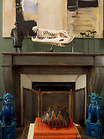Turquoise Chinese firedogs flank the fireplace in the drawing room, in front of which sits a boldly patterned tortoiseshell on a stack of red books