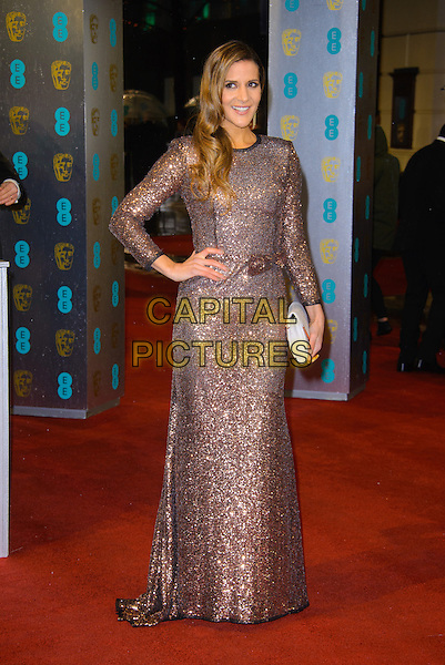 Amanda Bryam.EE British Academy Film Awards at The Royal Opera House, London, England 10th February 2013.BAFTA BAFTAS arrivals full length hand on hip clutch bag white gold bronze sparkly sequins sequined dress .CAP/CJ.©Chris Joseph/Capital Pictures