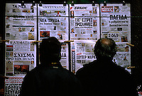 04 NOV 2003 - ATHENS, GREECE - Athenians read newspapers clipped to the side of a periptero sited on one of the cities side streets. (PHOTO (C) NIGEL FARROW)