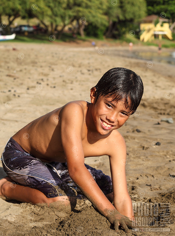 Boy playing in sand at Hanaka'o'o Beach (or Canoe Beach) on Maui.