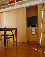 With the sliding doors open this compact kitchen is fully accessible and when they are closed the room works as a library