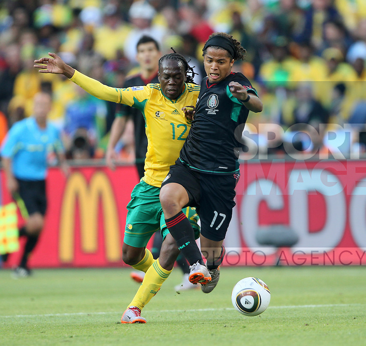 South Africa's Reneilwe Letsholonyane tussles with Mexico's Giovani Dos Santos