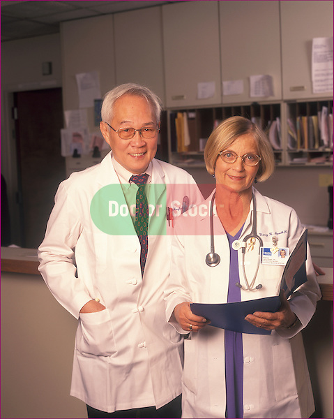 Portrait of an Asian-American MD and an RN at the desk of a medical clinic