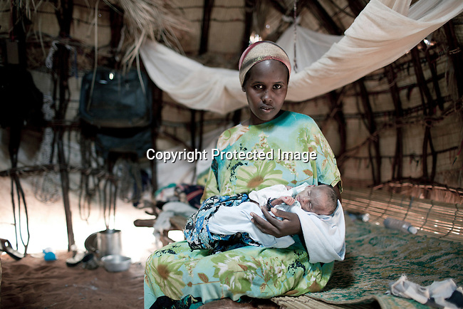 MATHAHALIBAH, KENYA - JULY 4: Amina Yare Isak holds her 3 month old daughter Umi Adan Olow, in her home on July 4, 2011 in Mathahalibah, Kenya. Earlier she went to a Save the Children outreach site in the location to weigh and check her child. The child weighed only 1,7 kilograms. The team examined about thirty children, among them some severely malnourished. Umis's mother brought her to the outreach site. The child has been sick a lot since birth. Amina Yare Isak, her mother, has two other children in the Save the Children nutrition program. The mother blames the drought for her children's sickness. Her livestock was finished and the lack of milk made her children malnourished. Two successive poor rains, entrenched poverty and lack of investment in affected areas have pushed millions of people into a fight for survival in the Horn of Africa. This is the driest this area have been since sixty years. (Photo by Per-Anders Pettersson)