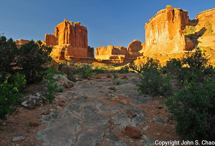 Early morning sun highlights massive sandstone rock monoliths in Park Avenue, a canyon in Arches National Park, Utah.