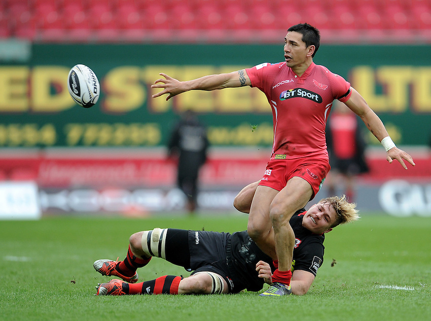 Scarlets' Regan King off loads while under pressure from Edinburgh's David Denton<br /> <br /> Photographer Ian Cook/CameraSport<br /> <br /> Rugby Union - Guinness PRO12 - Scarlets v Edinburgh - Saturday 28th March 2015 - Parc y Scarlets - Llanelli<br /> <br /> &copy; CameraSport - 43 Linden Ave. Countesthorpe. Leicester. England. LE8 5PG - Tel: +44 (0) 116 277 4147 - admin@camerasport.com - www.camerasport.com