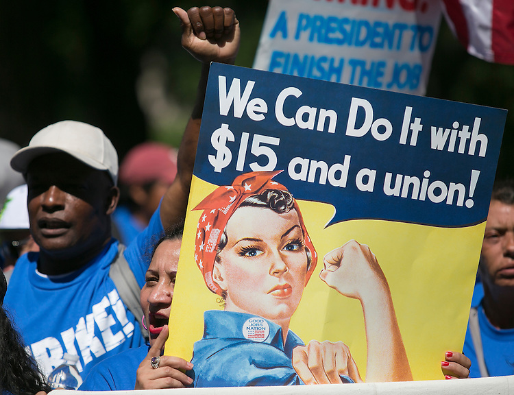 UNITED STATES - JULY 22: A protestor holds a sign in Upper Senate Park during a rally on Capitol Hill in Washington, Wednesday, July 22, 2015, to push for a raise to the minimum wage to $15 an hour. (Photo By Al Drago/CQ Roll Call)