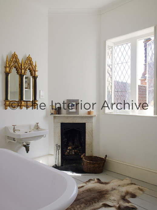 A small bathroom still has room for quirky touches such as an antique gilded mirror above the wash basin and the animal skin rug serving as a bath mat next to the roll-top bath