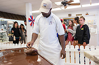 People watch as Daniel Ferguson, 50, shapes fudge at Murdick's Fudge in Edgartown, Martha's Vineyard, Massachusetts, USA. Ferguson is from Jamaica and has an H2B seasonal foreign worker visa. He says 2017 is his sixth summer season working in the fudge shop. During off-months, he returns to Jamaica where he can be with family and escape the cold weather. Most of the shop's workers are seasonal foreign workers. Other companies on Martha's Vineyard and around the US had difficulty obtaining H2B visas, but Murdick's Fudge received all it requested.
