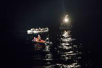 Die Sea Watch-2 Crew war am Freitag den 21. Oktober 2016 in den fruehen Morgenstunden waehrend ihrer 13. SAR-Mission vor der libyschen Kueste zu einer Position ausserhalb der 12 Meilenzone gerufen worden. Es war ein Fluechtlingsschlauchboot gesichtet worden. Als die Sea Watch-2 dort eintraf sah sie ca. 150 Menschen zusammengepfercht in einem ueberfuellten Schlauchboot sitzen. Eine Versorgung der Menschen auf dem Fluechtlingsschlauchboot mit Rettungswesten durch die Rettungs Boote der Sea Watch-2 wurde von der libyschen Kuestenwache unterbunden. Ein Soldat der Kuestenwache enterte das Schlauchboot vom Bug und machte sich dann an dem Aussenbordmotor zu schaffen. Auf dem Weg dahin schlug und trat er die Gefluechteten ein. Nach einigen Minuten entfernte sich das Boot der Kuestenwache. Dann verlor der Bug des Schlauchbootes seine Luft und es brach Panik bei den Gefluechteten aus. Sie sprangen in das Wasser und versuchten zum Schiff Sea Watch-2 zu gelangen. Die Crew warf ihnen Schwimmwesten und Rettungsringe zu, die Besatzungen der Rettungsboote der Sea Watch-2 zogen Menschen aus dem Meer, dennoch sind bis zu 30 Menschen ertrunken. Vier Ertrunkene konnten von der Sea Watch geborgen werden.<br /> Im Bild: Die Libysche Kuestenwache (rechts), das Fluechtlingsschlauchboot und ein Rettungsboot der Sea Watch-2 mit Schwimmwesten, an dem ein Mensch haengt der vor dem Soldaten aus dem Fluechtlingsschlauchboot gesprungen ist. Der Soldat der Kuestenwache lehnt hinten ueber die Backbordwand des Fluechtlingsschlauchbootes und sucht ihn.<br /> 21.10.2016, Mediterranean Sea<br /> Copyright: Christian-Ditsch.de<br /> [Inhaltsveraendernde Manipulation des Fotos nur nach ausdruecklicher Genehmigung des Fotografen. Vereinbarungen ueber Abtretung von Persoenlichkeitsrechten/Model Release der abgebildeten Person/Personen liegen nicht vor. NO MODEL RELEASE! Nur fuer Redaktionelle Zwecke. Don't publish without copyright Christian-Ditsch.de, Veroeffentlichung nur mit Fotografennennung, sowie geg