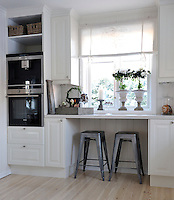 A kind of breakfast bar has been created beneath the kitchen window furnished with a pair of industrial-style stools