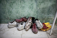 A pile of shoes, covered in blood from wounded and dead residents, sits at the entrance of an emergency ward at the Dar Al-Shifa hospital of Aleppo, Syria. November 01, 2012.