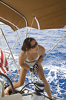 Young Asian local woman in bikini grinding winch while sailing a yacht off Hawaii
