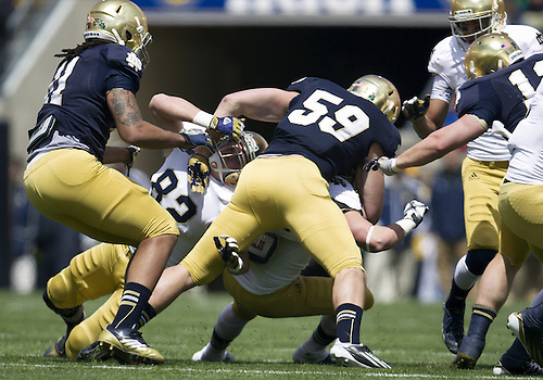 April 20, 2013: Notre Dame Fighting Irish inside linebacker Jarrett Grace (59) makes the tackle during the Notre Dame Blue-Gold Spring game at Notre Dame Stadium in South Bend, Indiana.  The Defense topped the Offense by a score of 54-43.