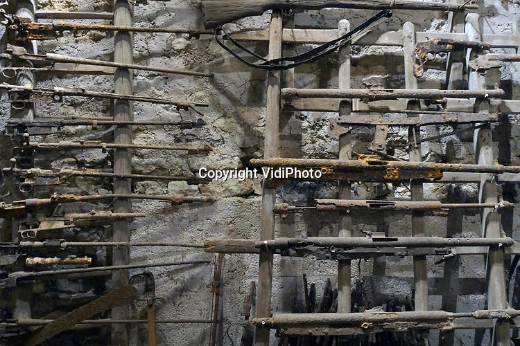 Foto: VidiPhoto<br /> <br /> ROMAGNE &ndash; Bij de Slag om Verdun in 1916 tijdens de Eerste Wereldoorlog, is er zoveel oorlogsmaterieel achtergebleven, dat de akkers en bossen er nu nog mee bezaaid liggen. Dat trekt jaarlijks tienduizenden verzamelaars naar de voormalige oorlogsvelden, onder wie opmerkelijk veel Nederlanders. Officieel is het verboden oorlogsrestanten op te graven of te zoeken, mede vanwege ontploffingsgevaar. Wie betrapt wordt kan een boete krijgen van 7200 euro. Volgens de Nederlandse museumeigenaar Jean-Paul de Vries van museum Romagne &rsquo;14-&rsquo;18, wordt er &ldquo;goudgeld&rdquo; betaald voor bijzondere vondsten. Een puntgave Duitse helm uit de eerste periode van de &ldquo;Great War&rdquo;, zoals de Eerste Wereldoorlog internationaal bekend staat, &lsquo;doet&rsquo; al snel 1250 euro. Zelf zoekt hij al 42 jaar naar bodemvondsten met toestemming van grondeigenaren. Een deel daarvan wordt verkocht en een ander deel wordt in zijn museum ge&euml;xposeerd. Het laatste jaar krijgt hij veel -illegale- concurrentie van Polen, die verwachten snel rijk te worden. Dit jaar trekt Verdun en omgeving meer bezoekers dan ooit. In november is het namelijk precies 100 jaar geleden dat de wapenstilstand werd getekend tussen de geallieerden (Triple Entente) en de Centrale Mogendheden. De Eerste Wereldoorlog eiste 8,5 miljoen levens. Foto: Gevonden geweren uit de Eerste Wereldoorlog in museum Romagne '14-'18.
