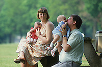 Mother, father and twin babies sitting on a park bench.
