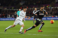 (L-R) Ki Sung Yueng of Swansea chases a Watford player during the Barclays Premier League match between Swansea City and Watford at the Liberty Stadium, Swansea on January 18 2016